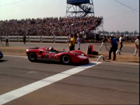 Champion spark plugs flag flying from flagpole tilt down to crowd lining pit alley at Riverside International Raceway / Bruce McLaren driving McLaren...