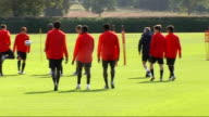 Arsenal training ahead of FC Porto match ENGLAND London Colney EXT Back view of Arsenal squad walking out onto pitch for training session / back view...