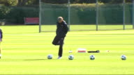 Arsenal training ahead of FC Porto match Wide shot of Wenger chatting to another coach on pitch / wide shot of Wenger kicking footballs about