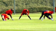 Arsenal training ahead of FC Porto match Wide shot of Arsenal footballers warming up and doing stretches on pitch