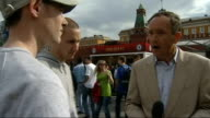 Fans arrive in Moscow RUSSIA Moscow Red Square EXT Reporter to camera and interviews with two Manchester United fans SOT