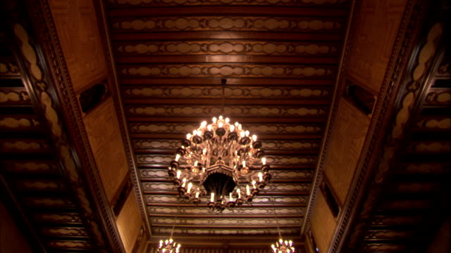 A chandelier hangs from a wood paneled ceiling of an ornate art deco cinema foyer. Available in HD.
