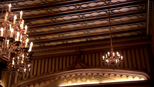 Chandeliers hang from an ornately carved wooden ceiling in an art deco former London cinema. Available in HD.