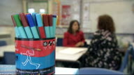 report from Leicester INT Close Shot of feet of children Setup shots of reporter and head teacher seaed including being seen through abacus Claire...