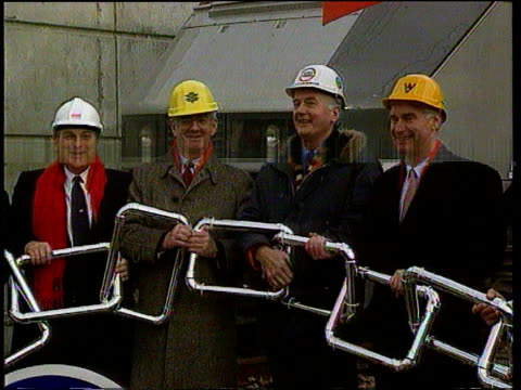 Channel Tunnel operators promise price war with ferry companies TX Executives standing holding links of symbolic chain for photocall at handover...