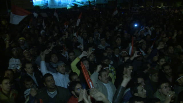 PAN Chanting spectators waving hands and flags in air in Tahrir Square during Mubarak's speech / Cairo Egypt