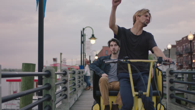 WS SLO MO. Charismatic bike taxi driver pumps fist in air on riverfront boardwalk.