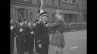 Charles de Gaulle President of Free French Committee accompanied by officer walks along front of formation of Allied soldiers inspecting them / CU de...