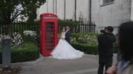 Charles Qian and his fiance Echo Li pose during a prewedding photography shoot at an iconic red telephone booth on October 11 2016 in London England...
