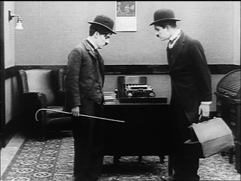 Charlie Chaplin and similarly dressed man mirroring each other's actions