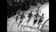 Charlie Green of Nebraska takes the 60 yard dash at the Los Angeles Indoor Track Meet / bleacher packed crowd applaud / famed Kenyan runner Kipchoge...