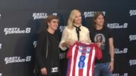 Charlize Theron receives an Atletico de Madrid shirt from Atletico de Madrid players Antoine Griezmann and Filipe Luis during a photocall for 'Fast...
