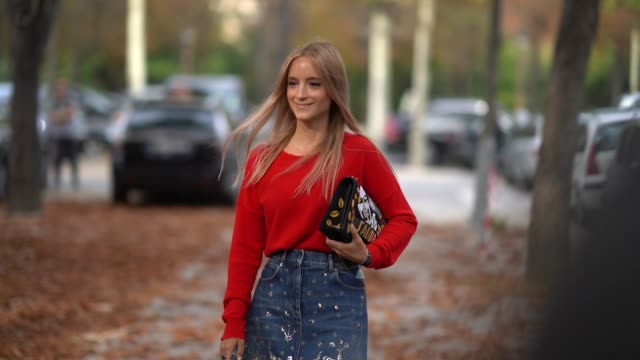 Charlotte Groeneveld wears a red top a black embroidered bag a denim embroidered skirt outside the Rochas show during Paris Fashion Week Womenswear...