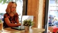 Charming blonde businesswoman in morning cafe using laptop
