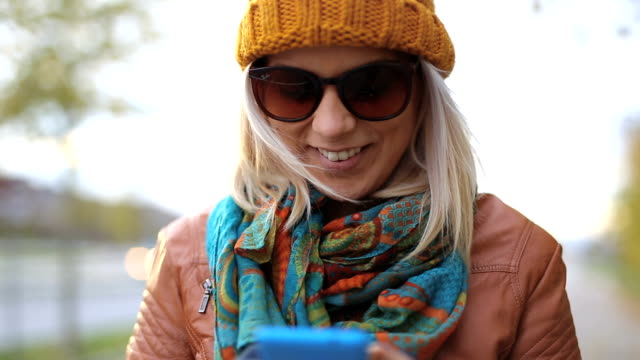 Charming blonde using smartphone. Close up.