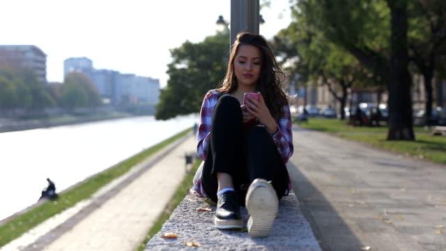 Charming woman using smartphone near river