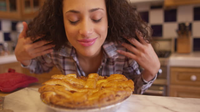 Charming young mixed ethnic woman smelling apple pie