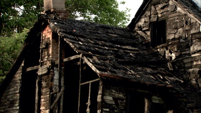 A charred shell is all that remains of a burnt-out home. Available in HD.