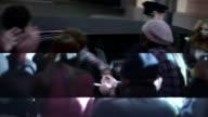 Chauffeur opens limousine door, hip-hop artist signs autographs for fans at awards show