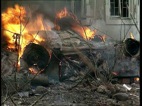 Grozny car bomb CHECHNYA Grozny CMS Burning wreckage GV Extensive damage in street PAN RL debris and burning wreckage in b/g and more wrecked cars in...