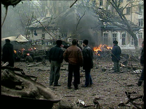 Grozny car bomb ITN CMS SIDE another woman carrying injured girl toddler to BV CMS Old lady in glasses and scarf round head with injured face PULL...