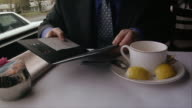 Check being handed to businessman at restaurant / man removing credit card from wallet and inserting in check holder