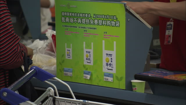 CU Checkout counter with labels promoting environmentally friendly shopping bags, Beijing, China