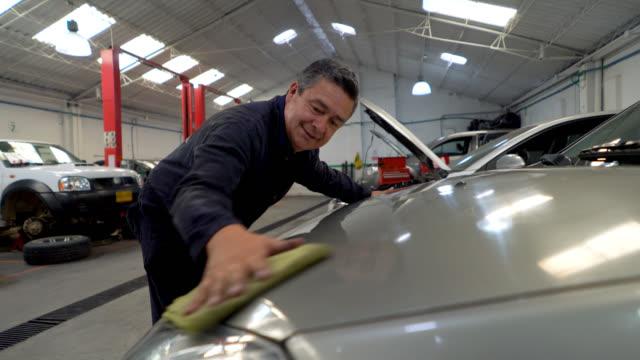 Cheerful adult man cleaning a car at a car dealership