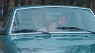 Cheerful couple driving retro car
