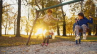 SLO MO Cheerful family swinging in the park