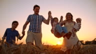 SLO MO Cheerful family walking in wheat field at sunset