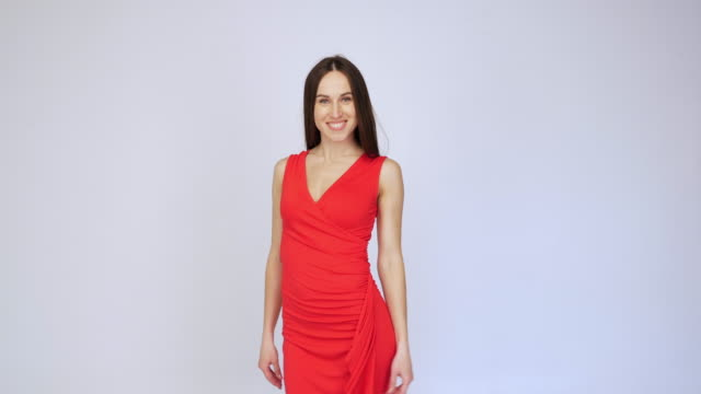 Cheerful female in red dress passing by