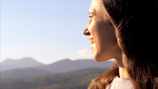 Cheerful female observing picturesque landscape at sunset