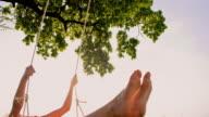 SLO MO Cheerful girl swinging on a tree swing