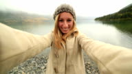 Cheerful girl takes selfie portrait near lake on a foggy day