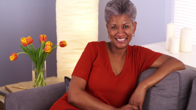 Cheerful grandmother sitting on couch