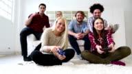 Allegro gruppo di giovani amici giocare videogiochi