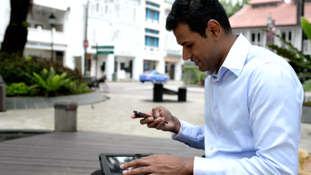 Cheerful Indian Businessman Multi-tasking with Digital Tablet and Phone