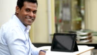 Cheerful Indian Businessman using Digital Tablet at Outdoor Cafe