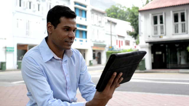Cheerful Indian Businessman using Digital Tablet at Outdoor