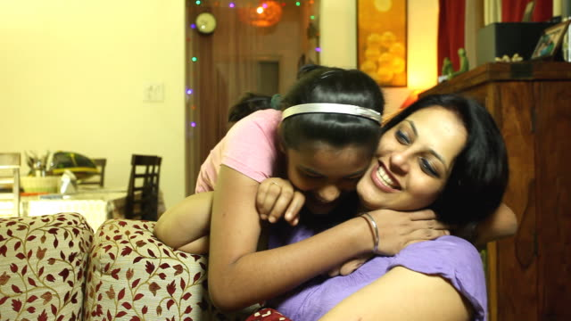 Cheerful Indian mother and daughter embracing having fun