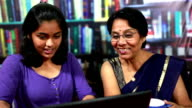 Cheerful Indian Senior Woman and Teenager Girl Using Laptop