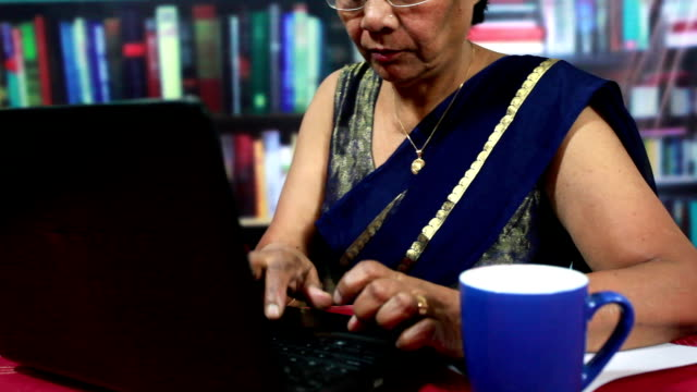 Cheerful Indian Senior Woman Using Laptop in a Library