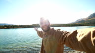 Cheerful man in nature takes selfie portrait near lake