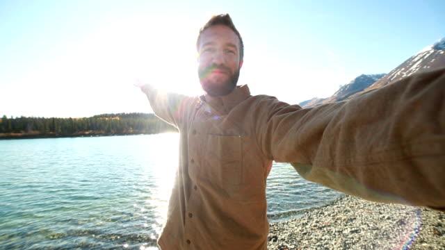 Vrolijk mens in de natuur neemt selfie portret in de buurt van lake