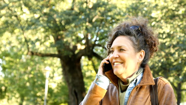 Cheerful mature Caucasian female on mobile phone in park 4K