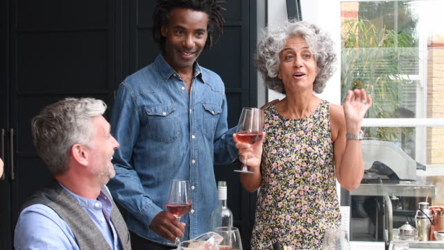 Cheerful mature couple at informal dinner party toasting with friends
