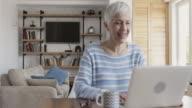 Vrolijke volwassen vrouw met laptop en video praatje met iemand.