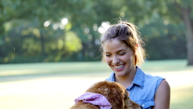 Cheerful mid adult Caucasian woman plays with dog in dog park