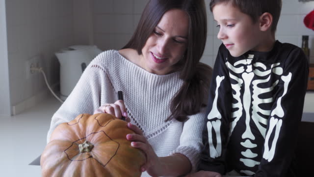Cheerful mother and son drawing eyes and mouth on pumpkin to carve